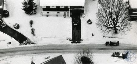 Image: di83166 - Aerial view of several people trying to push a small car out of snow along a street in Fort Wright.