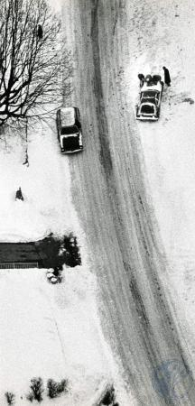 Image: di83168 - Aerial view of three people trying to push this car out of the snow in Fort Wright while a fourth person....