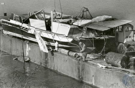 Image: di83637 - Albert Robinson, employee of Todd Marine SVC, unhooks crane from 50 foot Chris Craft house boat, center,....