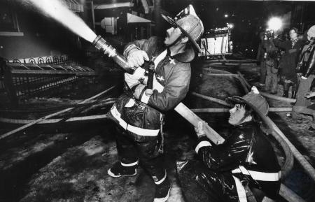 Image: di85674 - Covington fireman Gary Bowman and an unidentified fireman (also Covington) spray the hose on one of the....