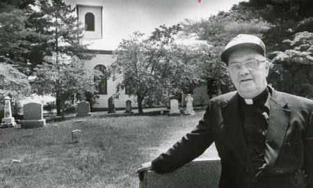 Image: di89409 - Father Henry Haacke in cemetary at St. Mary's Church where he is pastor.