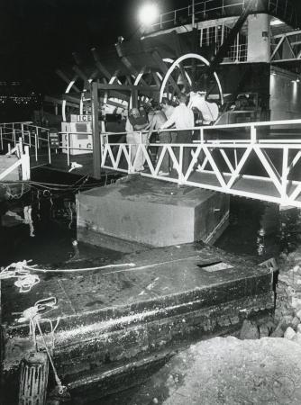 Image: di89617 - Ben Bernstein (in dark shirt), owner of the Mike Fink Restaurant, inspects the stern area of the boat....