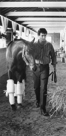 Image: di91378 - Peter Ortino, Asst. Trainer of Spend A Buck, walks the horse in the barn befor the race Friday Afternoon.....