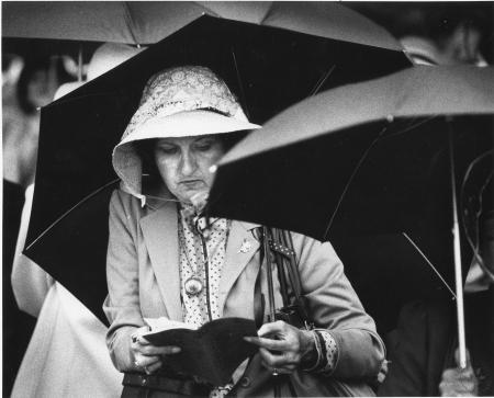 Image: di91385 - Unidentified lady at the Kentucky Derby 1983 tries to keep out of the rain that fell prior to the start....