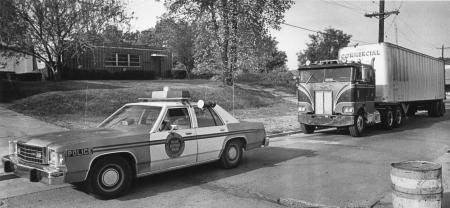 Image: di91726 - A Wilder police cruiser is parked on High Street in front of a truck. In mid-September 1983 this truck,....