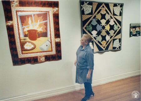 Image: di95626 - Arlene Gibeau, Carnegie Arts Center, checks out a quilt,
