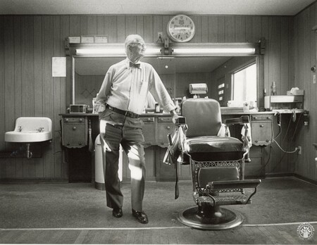 Image: di96231 - John Farrell, Crittenden barber, looking out the window of his barber shop. A new street and building....