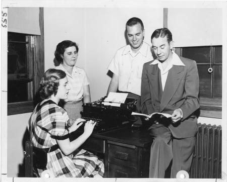 Image: kcpl046067022 - Four people gathered around a desk with a typewriter.
