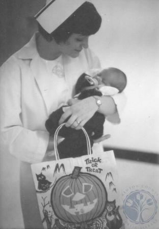 Image: ste001048037d - Pediatrics Halloween. Nurse holds a baby and a halloween bag during trick or treat.