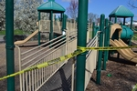 di128365 - Caution tape surrounds play equipment at ...