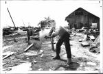 di50605 - Ed Peel sifting through rubble of his house ...