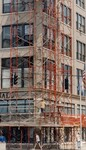 di97179 - Pedestrians walk under the scaffolding at ...